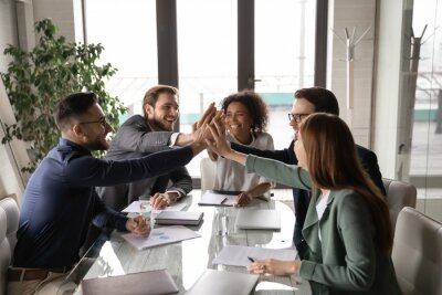 Fototapete Excited diverse business team giving high five at briefing, sitting at table in boardroom, motivated for shared success, overjoyed colleagues joining hands, engaged in team building activity