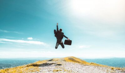 Fototapete Excited young businessman jumping keeping arms raised hiking the mountain peak - Celebrating success, winner and leader concept