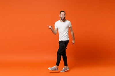 Fototapete Excited young man in casual white t-shirt posing isolated on bright orange wall background studio portrait. People sincere emotions lifestyle concept. Mock up copy space. Pointing index finger aside.