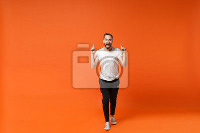 Fototapete Excited young man in casual white t-shirt posing isolated on bright orange wall background studio portrait. People sincere emotions lifestyle concept. Mock up copy space. Pointing index fingers up.