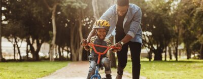Fototapete Father teaching his son cycling at park