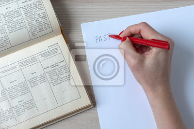 Female hand writes red pen on a white sheet of paper, on a wooden table an open English textbook. Top view, day, natural light from the window.