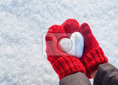 Fototapete Female hands in knitted mittens with heart of snow in winter day. Love concept. Valentine day background.