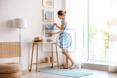 Fototapete Female interior designer decorating white wall with pictures indoors