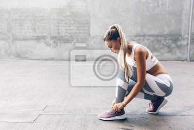 Fototapete Fitness sport woman in fashion sportswear doing workout over gray wall
