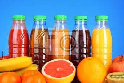 Flaschen Saft mit reifen Früchten auf blauem Hintergrund