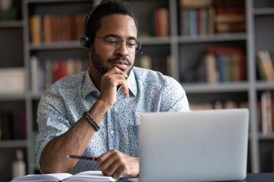 Fototapete Focused African man wear headphones with microphone looking at laptop screen listens audio lesson learn foreign language with tutor makes video call. Student watching webinar, e study on-line concept