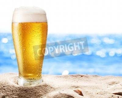 Fototapete Foto kaltes Bier botle in den Sand. Glitzernde Meer im Hintergrund.
