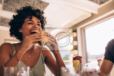 Fototapete Frau, die Burger am Restaurant essend genießt
