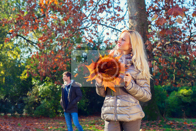Frau hält die Blätter im Herbst
