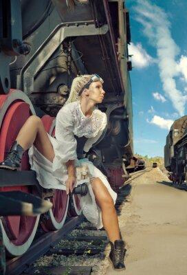 Fototapete Frau im Vintage-Kleid sitzt auf der Lokomotive das Rad.