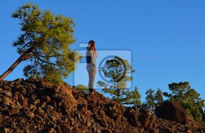 Frau / Mädchen auf einem Berg mit blauem Himmel.