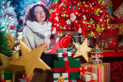 Frau mit einem schönen Weihnachtsbaum und Geschenke