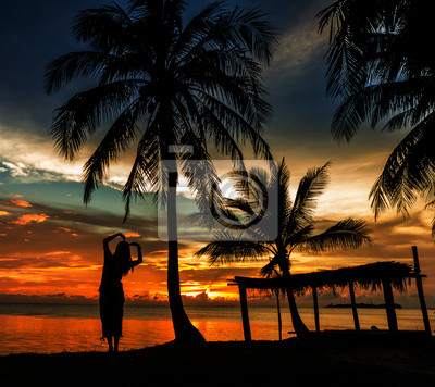 Frau mit Kokospalmen in silluate Hintergrund
