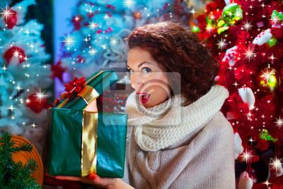 Frau öffnet das Geschenk vor dem Weihnachtsbaum