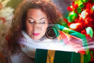 Frau öffnet eine glänzende Geschenk-Box mit Spannung
