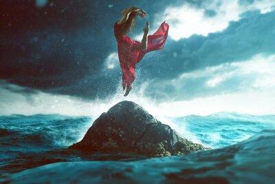 Fototapete Frau tanzt auf einem Felsen im Meer