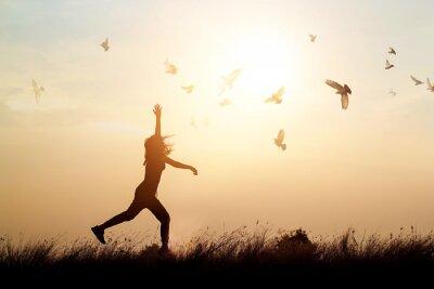 Fototapete Frau und fliegende Vögel genießen das Leben in der Natur auf Sonnenuntergang Hintergrund
