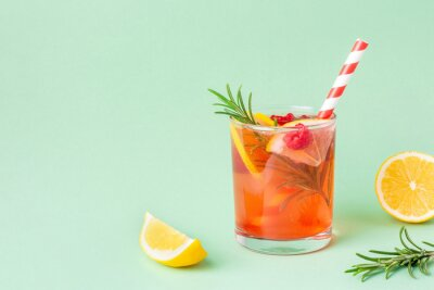 Fototapete Fresh red water with lemon and raspberry and rosemary on green background. Exotic summer drink with citrus slices with copy space.