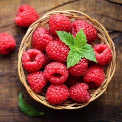 Fototapete Fresh ripe red raspberries in a wicjer bowl on dark rustic wooden background