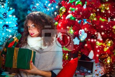 Freundin öffnet Geschenk vor dem Weihnachtsbaum