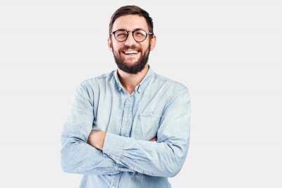 Fototapete Friendly face portrait of an authentic caucasian bearded man with glasses of toothy smiling dressed casual against a white wall isolated