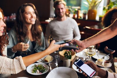 Fototapete Friends paying contactlessly in restaurant