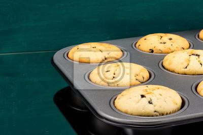 Fototapete Frisch gebackene Muffins im Backform grünerer Hintergrund