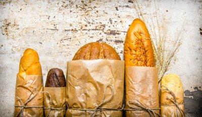 Fototapete Frisches Brot in Papier eingewickelt. Auf rustikalen Hintergrund.