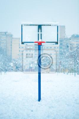 Frozen outdoor basketball hoop in winter snow