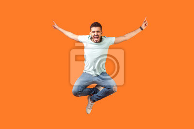 Fototapete Full length of crazy overjoyed brunette man in white outfit jumping in air with raised hands, screaming loud for joy, feeling energetic and lively. indoor studio shot isolated on orange background
