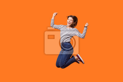 Fototapete Full length portrait of excited pretty woman with brown hair in casual shirt and denim jumping celebrating victory, raising fists showing yes gesture. indoor studio shot isolated on orange background