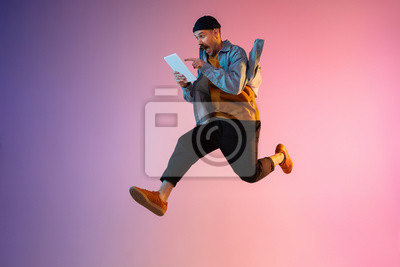 Fototapete Full length portrait of happy jumping man wearing casual clothes in neon light isolated on gradient background. Emotions, ad concept. Using tablet, hurrying up, late for work or sale, shopping.