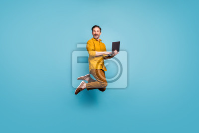 Fototapete Full size photo of funky man feel rejoice emotions jump use laptop search social media online black friday discounts wear casual style clothing isolated over blue color background
