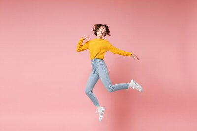 Fototapete Funny young brunette woman girl in yellow sweater posing isolated on pastel pink background in studio. People lifestyle concept. Mock up copy space. Having fun fooling around, looking aside, jumping.