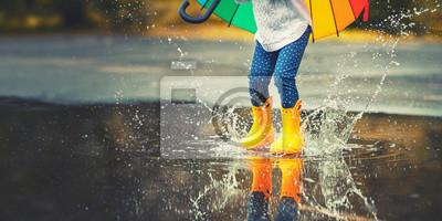 Fototapete Füße des Kindes in gelben Gummistiefeln springen über Pfütze im Regen