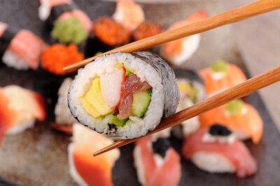 Fototapete Futomaki-Sushi von Stäbchen gehalten