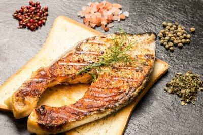 Fototapete Gegrilltes Lachsfilet über heißem Brotscheiben und Gewürzen über Schiefer