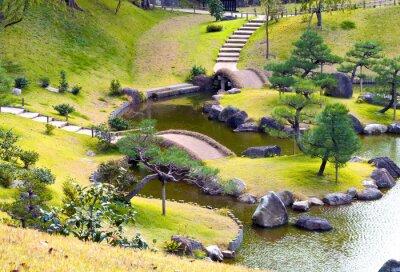 Fototapete Gepflegter hügeliger Felsgarten mit kleinen Brücken über gewundenen Bach, bergauf, Kiefern