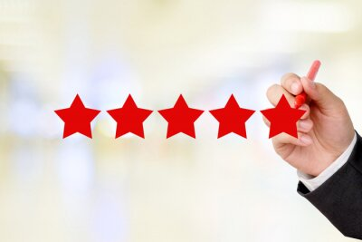 Geschäftsmann Hand schreiben roten Fünf-Sterne auf Unschärfe Hintergrund