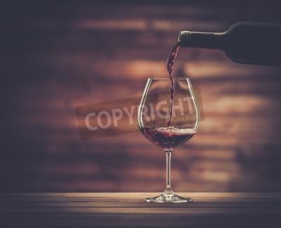 Fototapete Gießen Rotwein in das Glas vor Holzuntergrund
