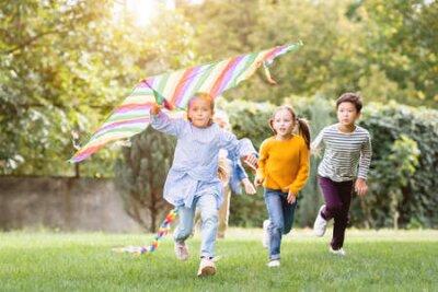 Fototapete Girl holding flying kite while running near multiethnic friends in park