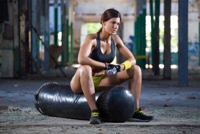 Fototapete girl seating on boxing bag