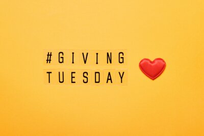 Fototapete Giving Tuesday text message. Global day of charitable giving after Black Friday shopping day. Red heart on yellow background
