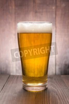 Fototapete Glas Bier auf dem hölzernen Hintergrund.