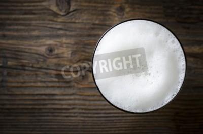 Fototapete Glas Bier Schaum über Holztisch