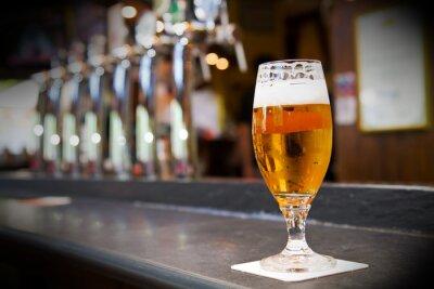 Fototapete Glas helles Bier auf einem dunklen Kneipe