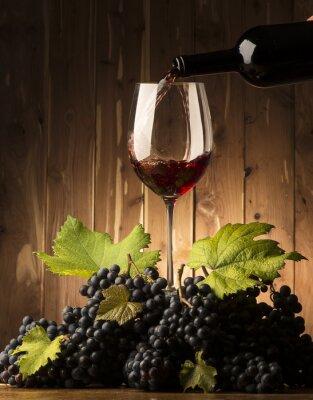 Fototapete Glas mit Rotwein und Grapeson der Holztisch