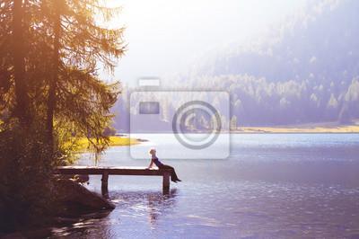 Fototapete Glückliche Frau sitzt auf dem Pier und lächelnd, Glück oder Inspiration Konzept, genießen das Leben