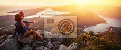 Fototapete Glückliches Paar, das den Sonnenuntergang in den Bergen überwacht